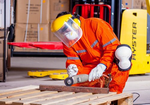 an industrial worker using a tool on a piece of metal