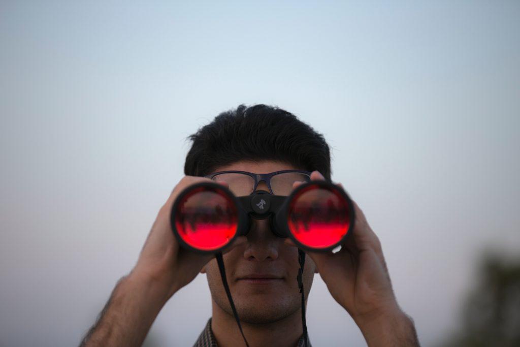 a man looking through a pair of binoculars