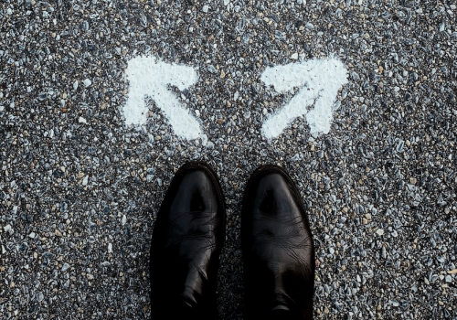 a pair of shoes in front of two arrows pointing in different directions